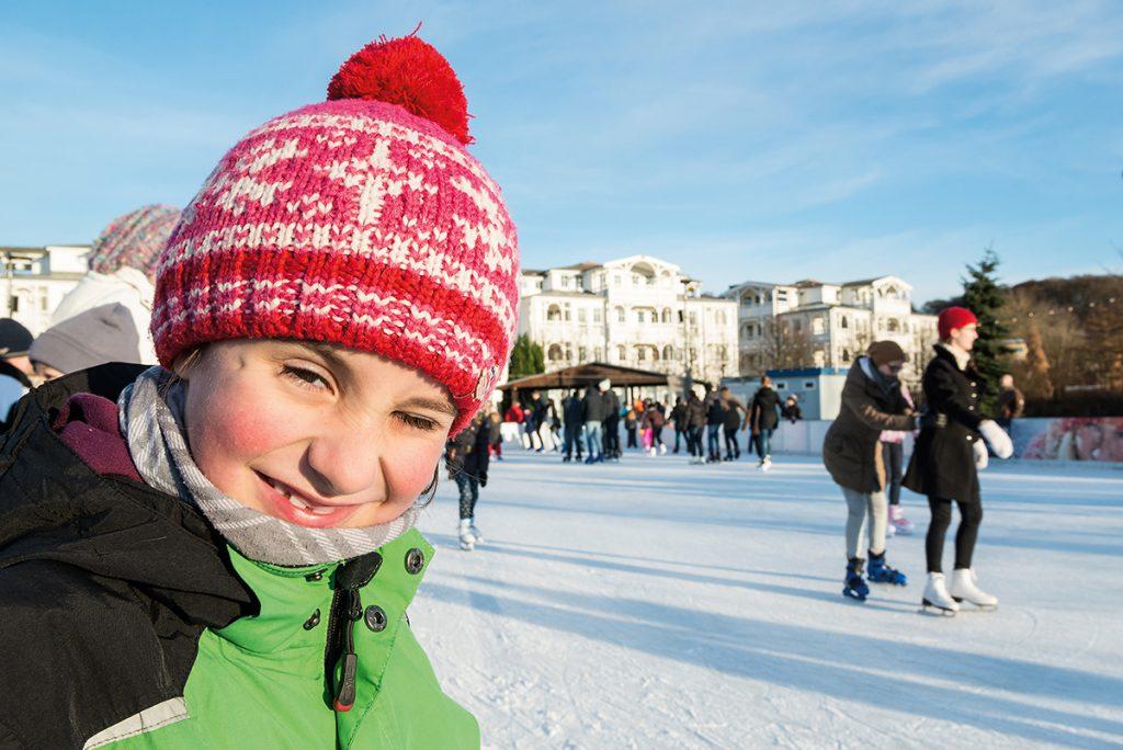 Leute auf der Eisbahn, Kind im Vordergrund