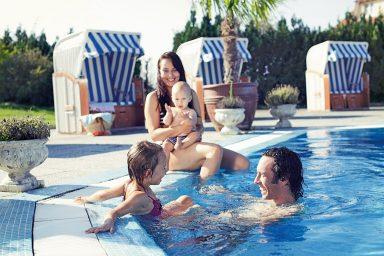 Familie mit Kindern am Pool