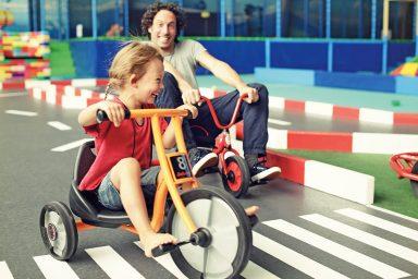 Vater und Kind auf Dreirädern