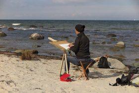 Malerin mit Zeichenbrett am Strand